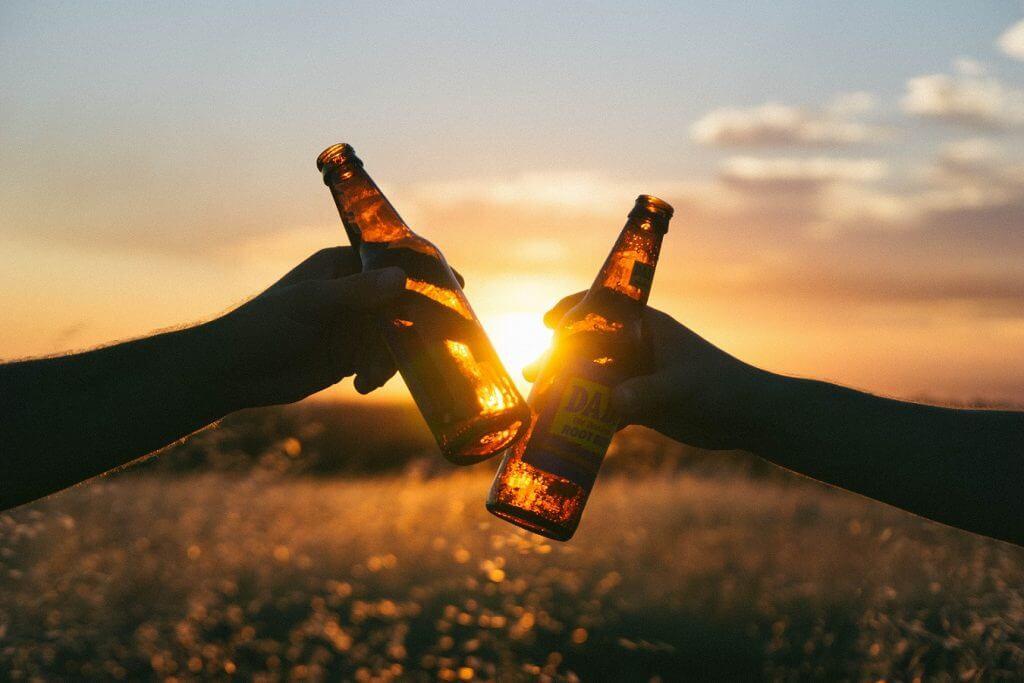 people holding root beer bottles cheersing